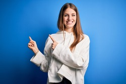 Young beautiful redhead sporty woman wearing sweatshirt over isolated blue background smiling and looking at the camera pointing with two hands and fingers to the side.