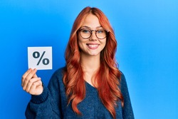 Young beautiful redhead woman holding percentage symbol looking positive and happy standing and smiling with a confident smile showing teeth