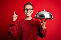Young beautiful redhead woman holding waitress tray over isolated red background surprised with an idea or question pointing finger with happy face, number one