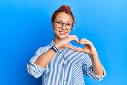 Young beautiful redhead woman wearing casual clothes and glasses over blue background smiling in love showing heart symbol and shape with hands. romantic concept.