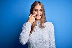Young beautiful redhead woman wearing casual sweater over isolated blue background Pointing with hand finger to face and nose, smiling cheerful. Beauty concept