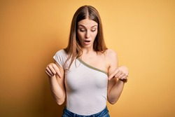 Young beautiful redhead woman wearing casual t-shirt over isolated yellow background Pointing down with fingers showing advertisement, surprised face and open mouth