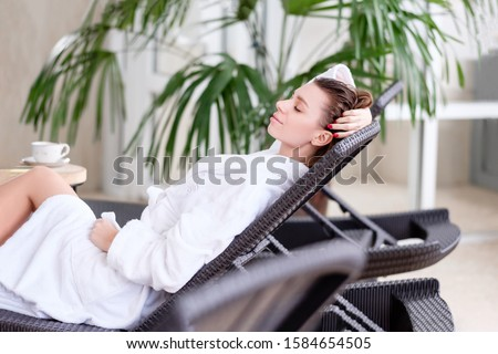 Young beautiful relaxed positive woman with eyes closed in white coat relaxing on a couch at a hotel. Concept of wellness and rehabilitation procedures