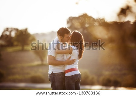 Young beautiful romantic couple in backlit composition