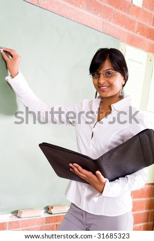 young beautiful school teacher write on blackboard