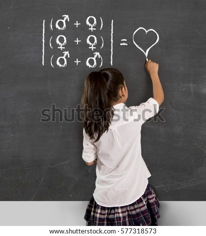 young beautiful schoolgirl in uniform holding chalk writing on blackboard standing for freedom of sexuality orientation supporting love for heterosexual and homosexual couples #577318573