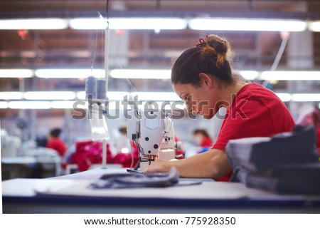 Young beautiful seamstress is working of cloth factory Foto stock ©