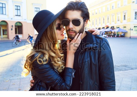 Young beautiful sensual blonde girl kissing her handsome stylish boyfriend. Pretty romantic couple wearing leather jackets, hat and sunglasses, rock biker style. Bright evening street sunlight.