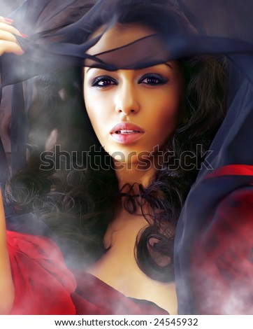 Young beautiful sexual woman in smoke clubs slightly opens a veil, showing the well-groomed person