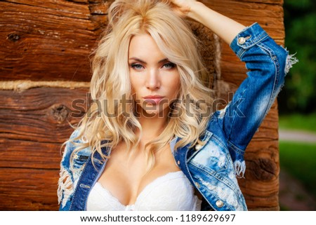 Young beautiful sexy blonde woman in jeans clothes and a white bra posing against a wooden wall background