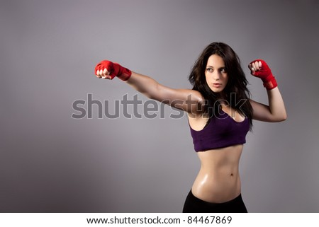 Young beautiful sexy boxer woman making kick with red boxing bandage on hands over gray background