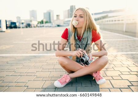 Young beautiful sexy fashionable hipster girl in shorts is resting sitting on the ground and blows bubbles of chewing gum and taking pictures. The concept of lifestyle