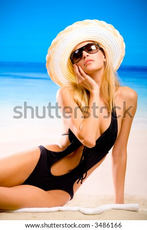 Young beautiful sexy tanned blond woman in hat and bikini laying on sea beach