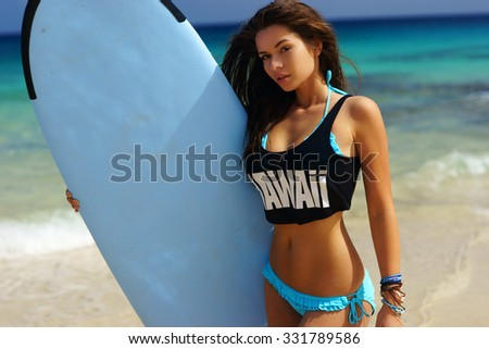 Young beautiful sexy woman in blue bikini and black t-shirt standing at sandy beach against blue water and holding surfboard. Surf girl