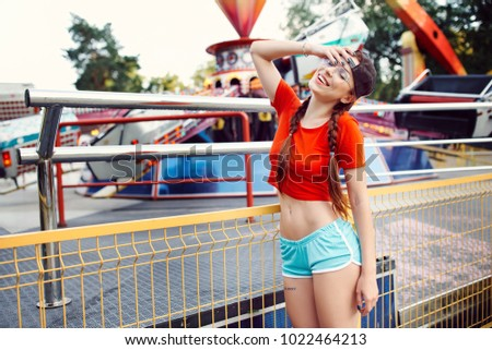 Young beautiful sexy woman in red virgin panties glasses baseball cap blue shorts white sneakers resting in summer in park with carousels