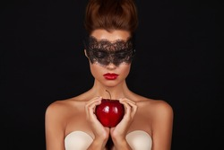 Young beautiful sexy woman with dark lace on eyes bare shoulders and neck, holding big red apple to enjoy the taste and are dieting, feeling temptation, teeth passion sex red lips