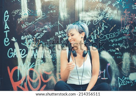 young beautiful short blue hair hipster woman with headphones music in the city #214356511