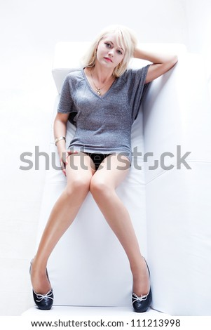 young, beautiful slim blonde girl in a gray jacket lying on a white sofa in a white studio