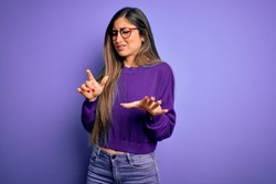 Young beautiful smart woman wearing glasses over purple isolated background disgusted expression, displeased and fearful doing disgust face because aversion reaction.