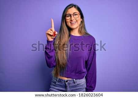 Young beautiful smart woman wearing glasses over purple isolated background showing and pointing up with finger number one while smiling confident and happy.