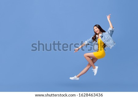 Young beautiful smiling Asian girl floating in mid-air with hand pointing up and down isolated on light blue background with copy space