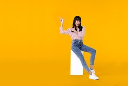 Young beautiful smiling asian girl hand pointing up to copy space isolated on yellow background.