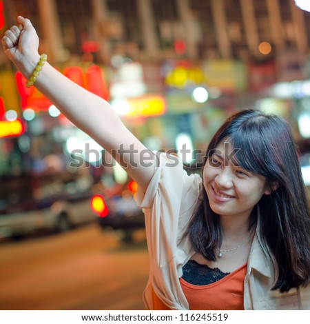 Young beautiful smiling Asian woman in street at night