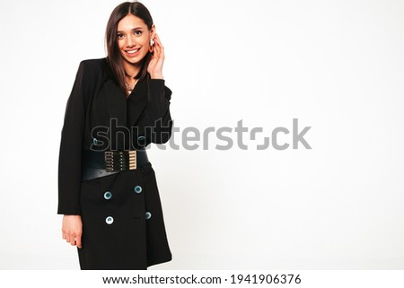 Young beautiful smiling brunette female in nice trendy black business suit.Sexy carefree woman posing on grey background in studio.Fashionable model with bright evening makeup having fun