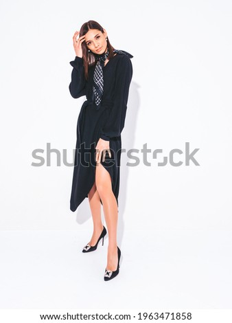 Young beautiful smiling brunette female in nice trendy black dress.Sexy carefree woman posing on grey background in studio.Fashionable model with bright evening makeup