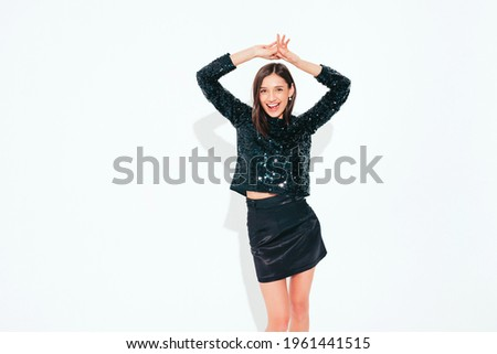 Young beautiful smiling brunette female in nice trendy black evening party clothes.Sexy carefree woman posing near white wall in studio.Fashionable model with bright evening makeup having fun. Dancing