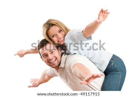Young beautiful smiling couple having fun together with piggyback and arms outstretched isolated on white background