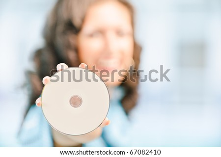 Young beautiful smiling dark-haired woman showing disk for data recording. Copy space.