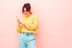Young beautiful smiling female in trendy summer yellow hipster sweater and jeans.Sexy carefree woman posing near pink wall in studio.Positive model having fun. Looking at smartphone screen, using app