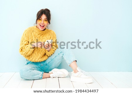 Young beautiful smiling female in trendy summer yellow hipster sweater and jeans.Sexy carefree woman sitting near blue wall in studio.Positive model having fun. Looking at smartphone screen, using app