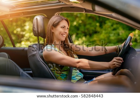 Young beautiful smiling girl driving a car.  #582848443