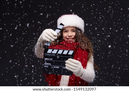 Young beautiful smiling girl in knitting pullover holding director's clapper board for making Christmas video in studio.Movie production clapper board.Lights, camera, action. Start of winter holidays.