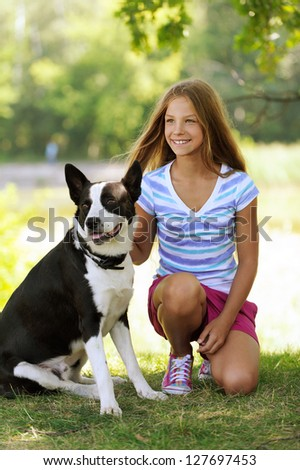 Young beautiful smiling girl with black dog, against green summer garden.