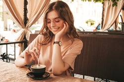 Young beautiful smiling hipster female in trendy summer clothes.Carefree woman sitting in veranda terrace cafe and drinking coffee.Positive model having fun and dreams
