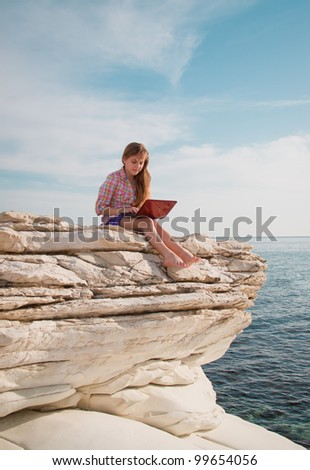 Young beautiful smiling teenage girl with computer on the beach/rocks with sea-view