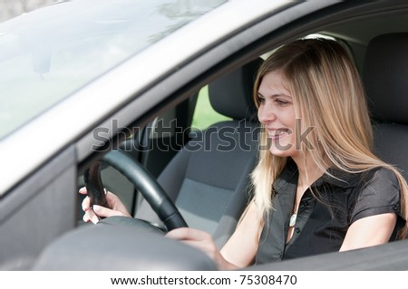 Young beautiful smiling woman driving car - portrait through side window