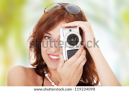 Young beautiful smiling woman holding a micro four thirds photo camera.