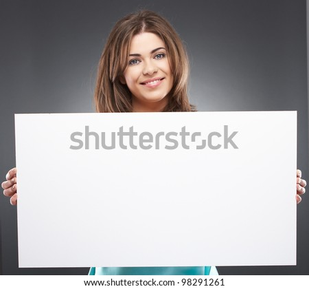 Young beautiful smiling woman holding white blank board, isolated over gray