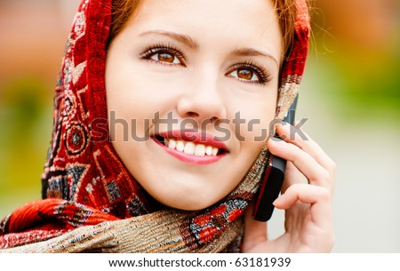 Young beautiful smiling woman in motley red headscarf talks on cellular telephone, against city structures.