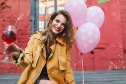 Young beautiful smiling woman in orange trench coat holding cocktail in hand happily looking in camera with pink balloons near in old cozy courtyard of cafe