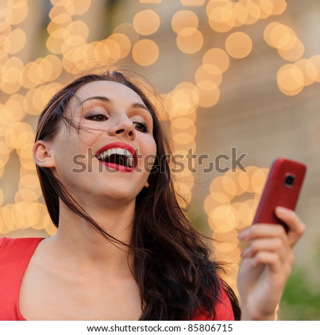 Young beautiful smiling woman in red dress reads text message on mobile phone against evening illumination.