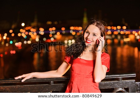 Young beautiful smiling woman in red dress talks on mobile telephone against the night Moscow Kremlin.