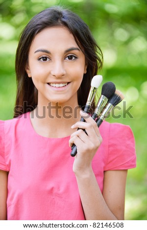 Young beautiful smiling woman in red dress with set make-up of brushes against green summer garden.