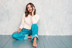 Young beautiful smiling woman looking at camera. Trendy female in casual summer jeans clothes. Positive female with red lips shows facial emotions. Cheerful model sitting near gray wall in studio