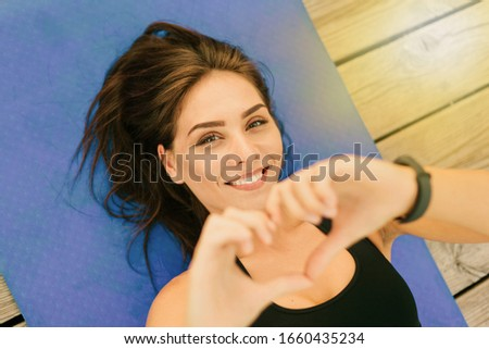 Young beautiful sport woman lies on mat and shows heart symbol by hands. Top view portrait Foto stock ©