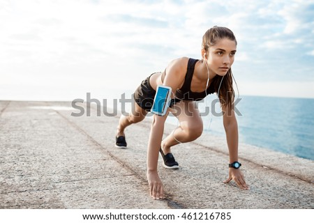 Young beautiful sportive girl preparing to run over seaside.